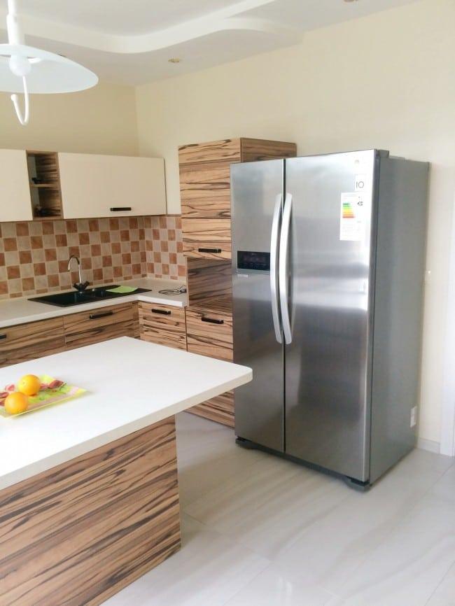Двухсекционный холодильник на угловой кухне под дерево