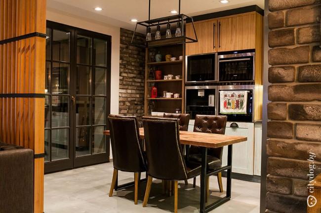 Обеденная зона в интерьере лофтовой кухни-гостиной с балконной дверью